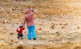 Kind, das seine Mutter auf dem Bergplateau begleitet Lizenzfreie Stockfotos