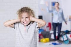 Kind, das seine Ohren abdeckt lizenzfreies stockfoto