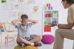 Kind, das seine Ohren während der Therapie bedeckt stockfotos
