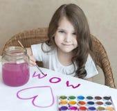 Kind, das selbst gemachte Grußkarte macht Ein kleines Mädchen malt ein Herz auf einer selbst gemachten Grußkarte als Geschenk für Stockbild
