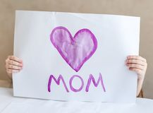 Kind, das selbst gemachte Grußkarte macht Ein kleines Mädchen malt ein Herz auf einer selbst gemachten Grußkarte als Geschenk für Stockfoto