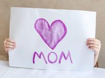 Kind, das selbst gemachte Grußkarte macht Ein kleines Mädchen malt ein Herz auf einer selbst gemachten Grußkarte als Geschenk für Lizenzfreies Stockfoto