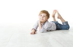Kind, das sich auf Fußboden hinlegt und Kamera betrachtet Stockbild