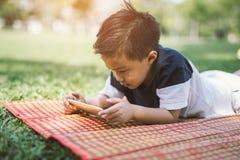 Kind, das Smartphone im Park spielt lizenzfreie stockbilder