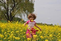 Kind, das Spaß auf canola Feld hat lizenzfreie stockfotos