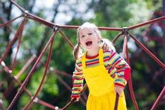 Kind, das Spaß auf Schulhofspielplatz hat Stockfotografie