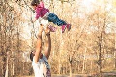 Kind, das Spaß mit dem Vater spielt im Sommerpark hat Vater, der oben sein Kind wirft Lizenzfreie Stockfotografie