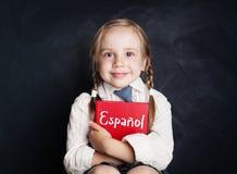 Kind, das Spanisch lernt Kleines Mädchen mit spanischem Buch stockfotografie