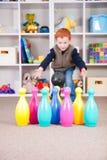 Kind, das Spiel mit Kinder rollenden Skittles spielt Lizenzfreie Stockfotos