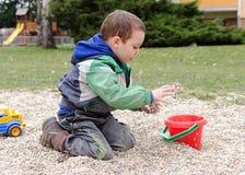 Kind, das Spielzeug und Steine im Park spielt Stockbild