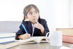 Kind, das stark mit Lehrbuch lernt und erforscht stockbilder