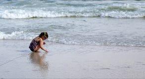 Kind, das am Strand spielt. Lizenzfreie Stockbilder