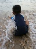 Kind, das am Strand spielt Stockfotografie