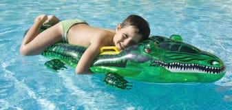Kind, das am Swimmingpool spielt Stockfotografie