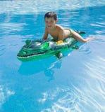 Kind, das am Swimmingpool spielt Lizenzfreie Stockfotografie