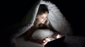 Kind, das Tablet in der dunklen Nacht, Mädchen-Graseninternet im Bett, nicht schlafend spielt stock footage