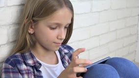 Kind, das Tablet, Kind Smartphone, Mädchen-Lesemitteilungen grasen Internet spielt stock video footage