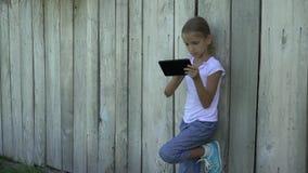 Kind, das Tablette durch das Zaunmädchen verwendet Kinder des Smartphone die im Freien studieren 4K spielt stock footage
