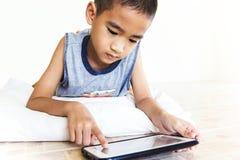 Kind, das Tablette 01 spielt Stockbild