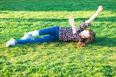 Kind, das unten Hügel im Gras rollt lizenzfreie stockfotos