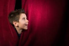 Kind, das unter dem Vorhang erscheint lizenzfreie stockfotografie