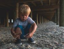 Kind, das unter einer Strand-Promenade spielt Stockfotos