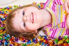 Kind, das unter Süßigkeiten liegt Stockfotos