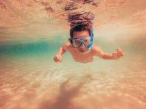 Kind, das unter Wasser mit Schwimmenmaske schwimmt Stockfotografie