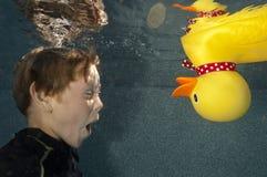 Kind, das Unterwasserwithi Spielzeugente schwimmt Stockfotografie