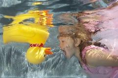 Kind, das Unterwasserwithi Spielzeugente schwimmt lizenzfreie stockbilder