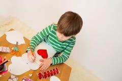 Kind, das Valentinstag-Handwerk tut: Herzen und Liebe Lizenzfreie Stockfotos