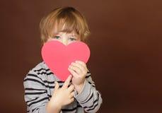 Kind, das Valentinstag-Herz-Zeichen hält stockfotos