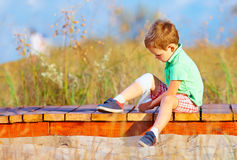 Kind, das verletztes Bein verbindet Stockfotos