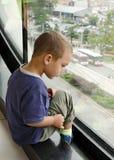Kind, das vom Fenster schaut Stockbild