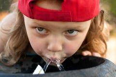 Kind, das vom Wasserbrunnen trinkt Stockbilder