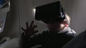 Kind, das VR-Kopfhörer im Flugzeug verwendet stock footage