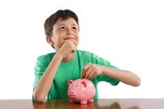 Kind, das was denkt, mit ihren Sparungen zu kaufen stockbild