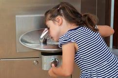 Kind, das Wasser-Brunnen vom im Freien trinkt Stockfoto
