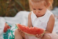 Kind, das Wassermelone im Garten isst Kleines M?dchen, das im Garten h?lt eine Scheibe der Wassermelone spielt Kindergartenarbeit lizenzfreies stockbild