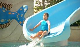 Kind, das Wasserrutsche spielt Stockfotos
