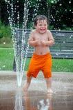Kind, das weg an einem heißen Sommertag abkühlt Lizenzfreie Stockfotografie