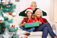 Kind, das Weihnachten mit seinen Großeltern feiert Stockfotos