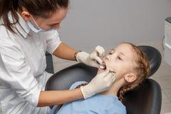 Kind, das zahnmedizinische Kontrolle durch Spezialisten im Zahnarztbüro hat lizenzfreies stockbild