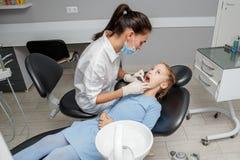 Kind, das zahnmedizinische Kontrolle durch Spezialisten im Zahnarztbüro hat stockfotos
