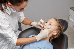 Kind, das zahnmedizinische Kontrolle durch Spezialisten im Zahnarztbüro hat stockbild