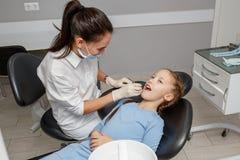 Kind, das zahnmedizinische Kontrolle durch Spezialisten im Zahnarztbüro hat stockfoto
