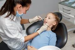 Kind, das zahnmedizinische Kontrolle durch Spezialisten im Zahnarztbüro hat lizenzfreie stockbilder