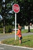 Kind, das zeigt, um Zeichen zu stoppen Stockfotografie