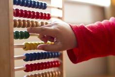 Kind, das Zählung unter Verwendung des Abakusses lernt Lizenzfreies Stockbild