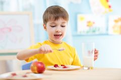 Kind, das zu Hause gesundes Lebensmittel isst Lizenzfreies Stockfoto